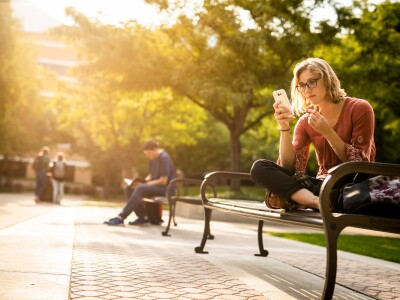 A woman receives a message on her phone while sitting on a bench outside on BYU's campus.