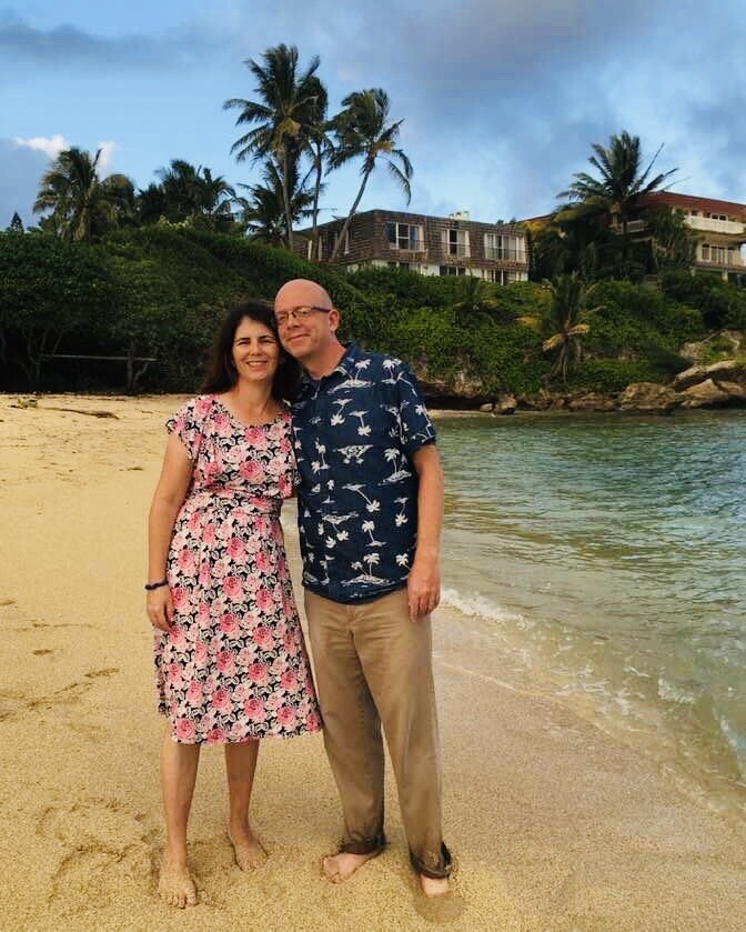 Suzanne and Matthew Bown standing together on the beach with trees and house in background.