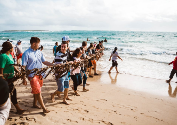 Students and staff at Hukilau Beach pulling a fishing net