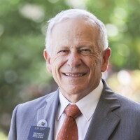 A portrait of Elder Weldon Sleight smiling at the camera with blurred green plants in the background.