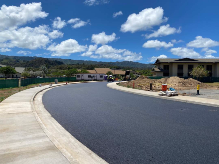 A close view of asphalt pavement on the roadway from Naniloa Loop side. The pavement and sidewalks look complete. Housing Office Building can be seen in the back.