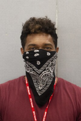 Photo of Kumar wearing a red shirt and lanyard with a head scarf around his face.