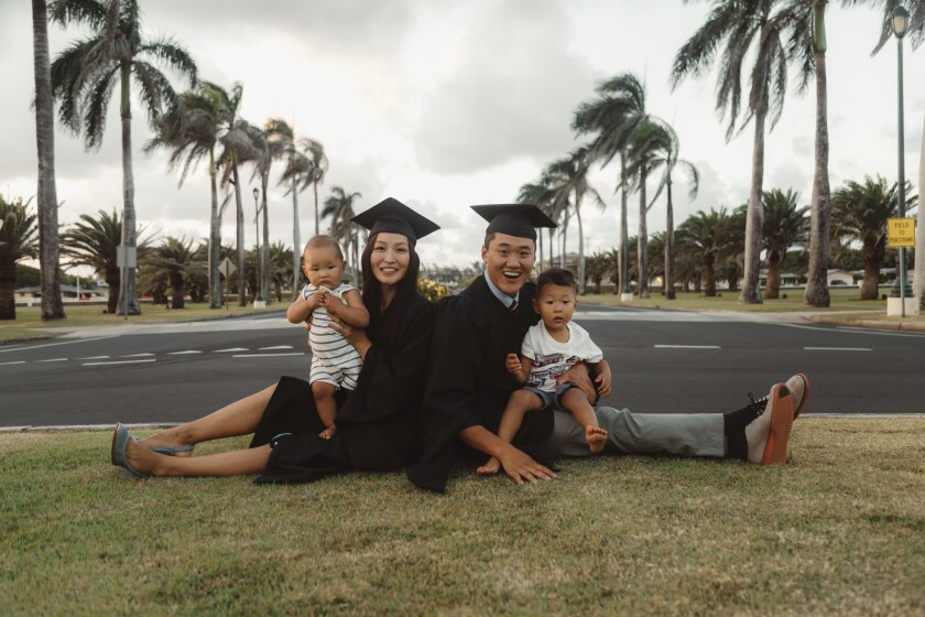 Purevdorj and Boldbaatar wear graduation black cap and gown while holding a baby and toddler sitting down in the grass with the road and palm trees in the background.