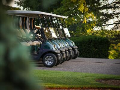 Five green golf carts lined up on a road