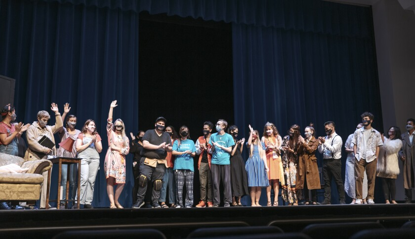 21 students on stage clapping, putting up their arms and looking at each other all wearing masks with a clear part in the middle of them.