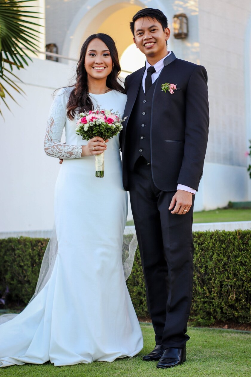 Sean and Anna Somoray pose in wedding attire after getting married.