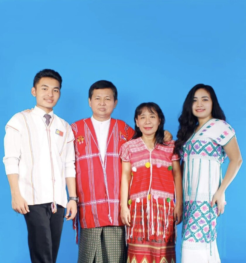 Su Myat (Rachel) Yadanar Shin (right) and her family stands in traditional clothing smiling with a blue background behind them.