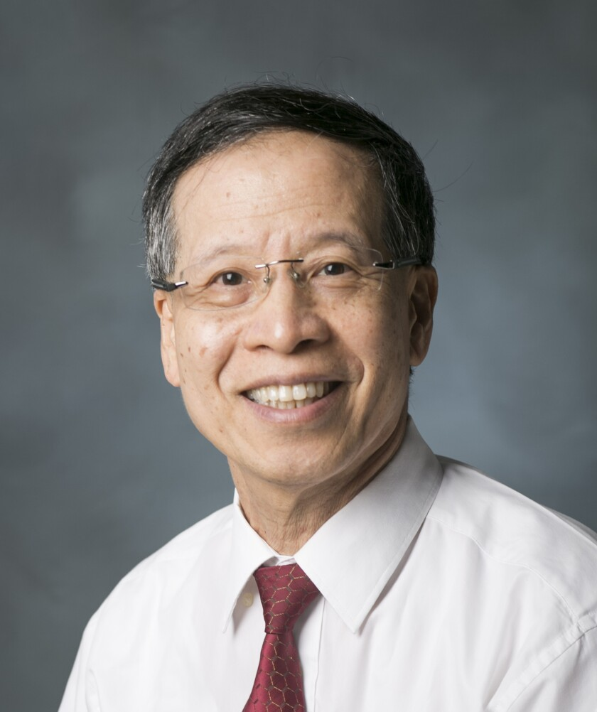 Sherman Han smiling wearing a white button up shirt and red tie with a grey background.