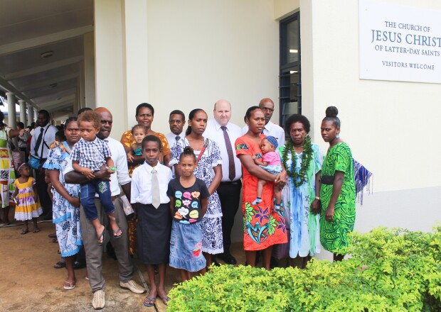 Ni-Vanuatu people in church clothes gather together in front of the Church of Jesus Christ of Latter-day Saints' chapel.