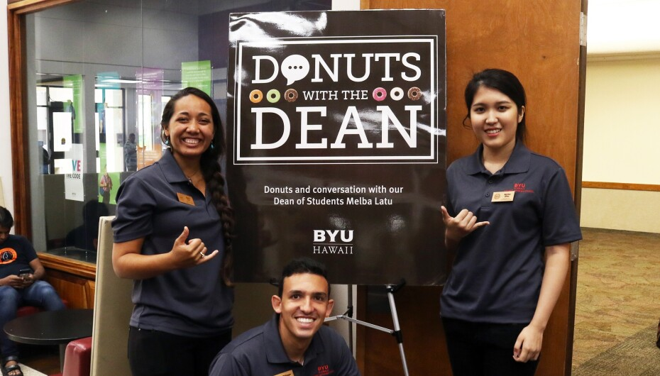 3 Student Employees Standing in front of Donuts with the Dean poster