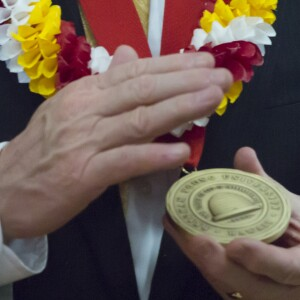 Hands holding a BYUH presidential medallion