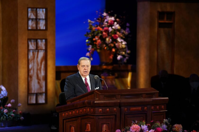 Elder Jeffrey R. Holland  speaking at a wooden pulpit with tan and brown walls with a big blue window and flowers behind him.