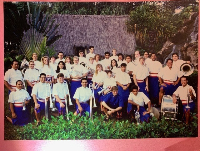 Photo of the BYUH brass band with Maiava in it with all the students wearing white button-up shirts and dark purple/blue buttons with trees and a hut behind them.