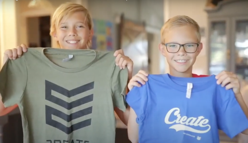 """Two boys, Tanner and Tate Smith, smile while holding up a green and a blue T-shirt with a black design and the word """"create"""" on them."""