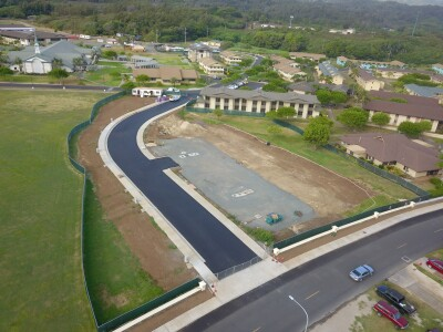 Aerial view of Mikionele Way Extension, and it is complete. Temple View Apartments are at the top and Naniloa Loop is at the bottom right corner of the photo. The extension is connecting the apartments and the loop. The two ends of the Mikionele Way is closed by fences.