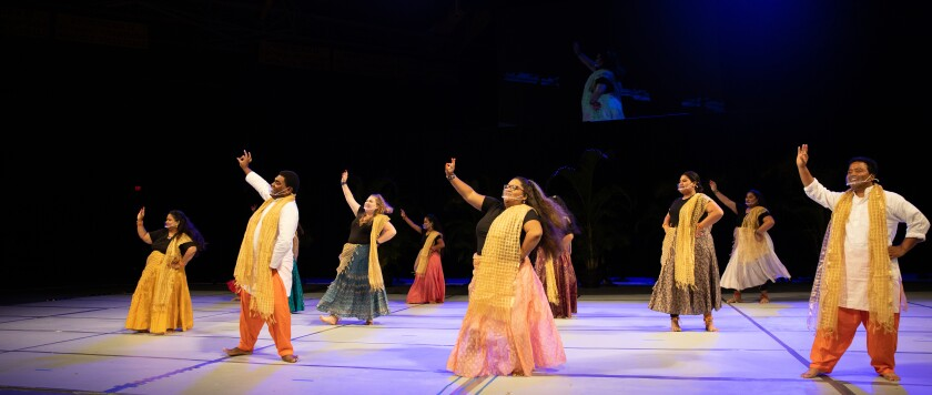 Men and women wearing multi-colored traditional Indian clothes dance putting their hand in the air standing on a white floor and black background behind them.
