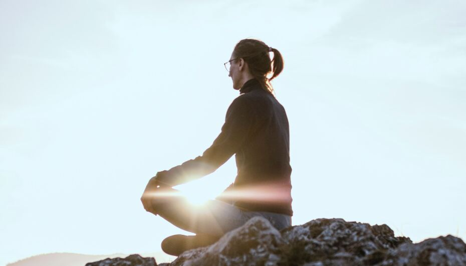 Image of female outdoors on a rock meditating