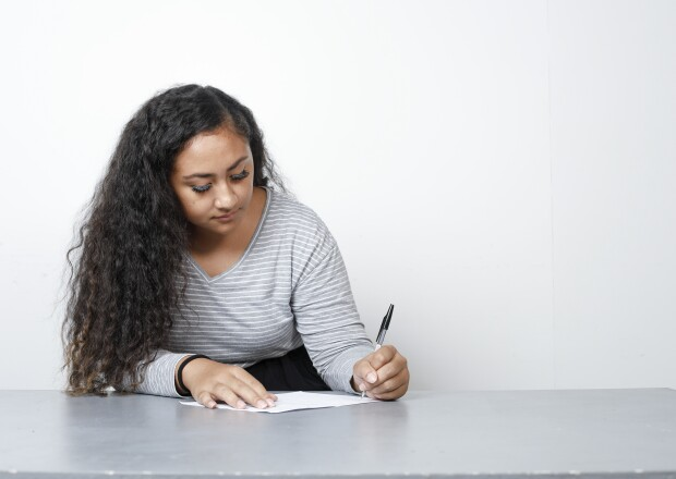 Image of a female student writing on paper
