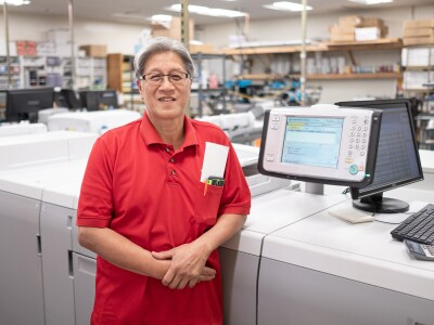 Iggy Santeco stands in front of a printer at a print shop.