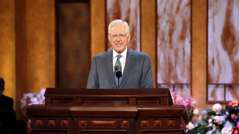Elder D. Todd Christofferson smiling speaking at a wooden pulpit with brown and tan walls and flowers behind him.