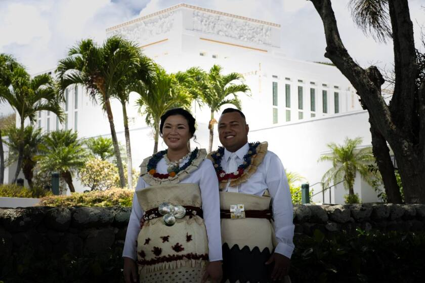 The Senilolis stand together in white temple clothes in front of the Laie Hawaii Temple wearing traditional Tongan leis and mats with mother of pearl and other embroidery.