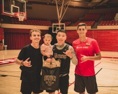 """Winner Bilguun Enkhbaatar wearing a black and yellow Lakers jersey holding his baby and a BYUH bag with two other men standing next to him wearing a black shirt and red shirt that says """"BYU–Hawaii"""" with a basketball court behind them."""
