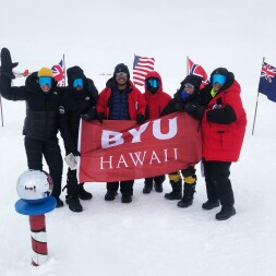 Participants in the Airbnb-Ocean Conservancy Antarctic Sabbatical holding a BYU–Hawaii flag in front of country flags at the South Pole