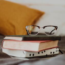 photo of glasses on top of stacked books