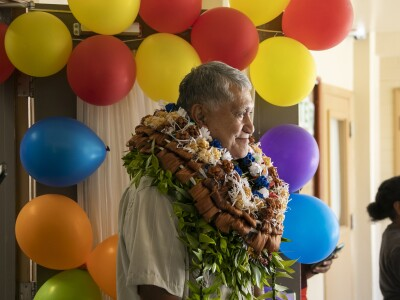Dr. Wesley smiling looking in front of him in a green aloha shirt with leis around his neck red, yellow, purple, blue and green balloons behind them.