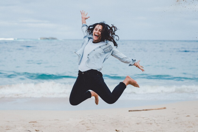 Davia Kaopua jumps in the air on a beach.