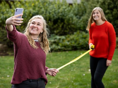 Image: Two students with a measuring tape between them take a selfie.