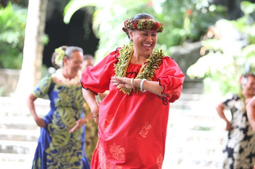 Aunty Kela smiles as she's dancing in a pink dress, lei and haku, with other dancers in background.