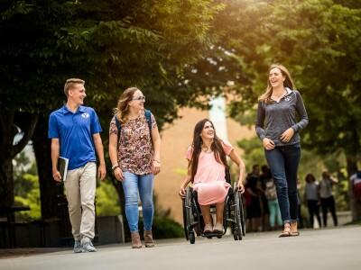 People Walking with lady in wheelchair