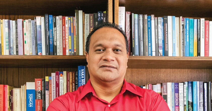 Tevita O. Ka'ili stands in front of a bookshelf wearing a red shirt