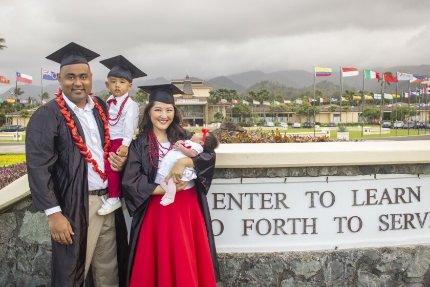 """Serena and Justin stand in black graduation caps and gowns standing in front of BYUH campus by the sign that says """"Enter to learn go forth to serve"""" while wearing white and red with leis."""