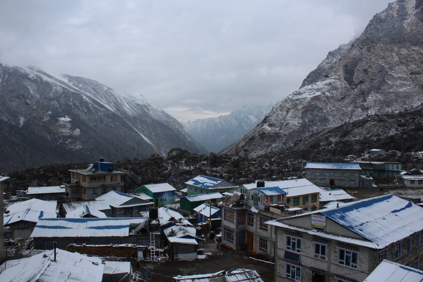 A town in Nepal with snow-covered mountains in the background.