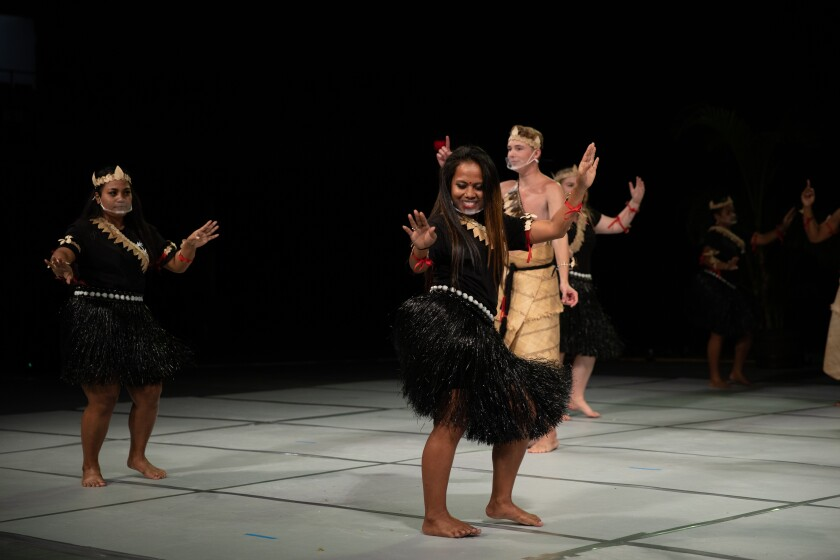Two woman in the front wearing black shirts and black grass-looking skirts shake their hips with a man behind them wearing mats around their waist and no shirt and other woman behind them.