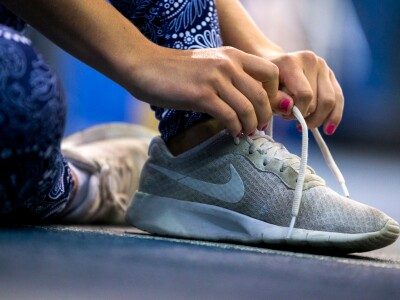 A woman laces up her sneakers