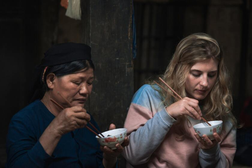 A Vietnamese women (wearing a black hat and dark blue shirt) sits next to a blonde women (wearing a pink and blue sweatshirt), both eating out of a small white bowl with chopsticks.