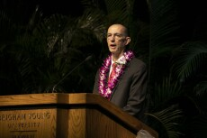 John Bell talks at a wooden podium wearing a black suit and red tie with a pink and white flower lei.