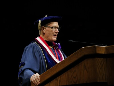 President John Tanner wearing a dark blue gown standing behind a podium with a dark background.