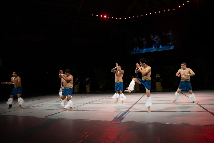 Men wearing blue skirts and white hanging clothe around their calves are clapping on a white stage with a black background with a screen behind them.