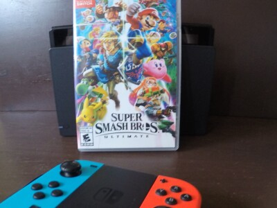 """A Nintendo Switch console, controller and """"Super Smash Bros. Ultimate"""" Switch game."""