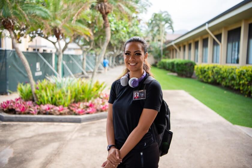 Tetuaapua mengenakan kemeja hitam dengan ide Pusat Kebudayaan Polinesia di dada, headphone ungu di leher, dan ransel hitam dengan tanaman hijau, bangunan, dan area konstruksi hijau di belakangnya.