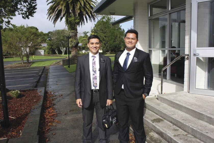 Two missionaries wearing suits, ties and missionary names tags, stand outside of a church building in New Zealand.