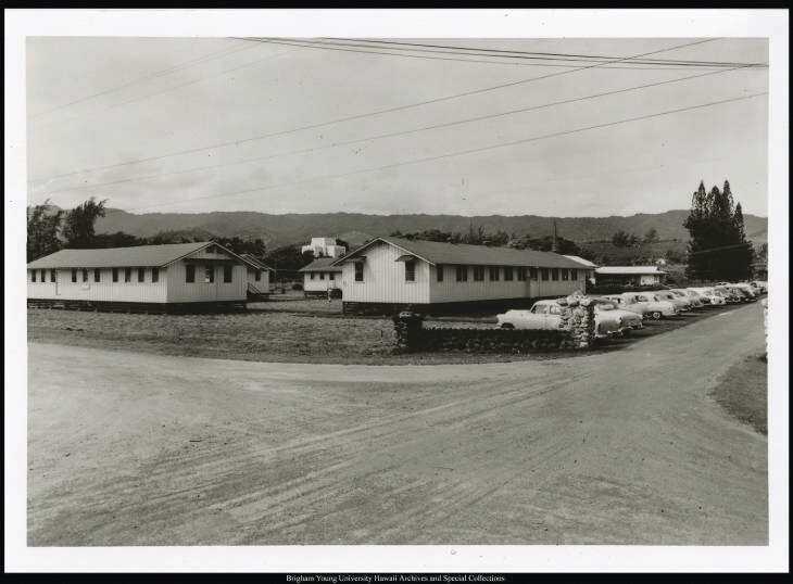 Old World War II army barracks were moved onto land in Laie for classrooms and more in the first days of BYU-Hawaii in the late 1950s when it was called the Church College of Hawaii. There are four barracks set on the property facing each other creating inside them a square filled with grass. A line of parked cars are on the right side of one of the barracks, and the Laie Hawaii Temple set up higher on a hill can be seen behind the buildings. The barracks are at the crossroads of two dirt streets.