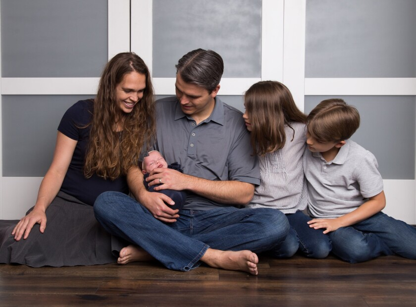 Shenley Puterbaugh sits next to her husband and two children with her husband holding a baby in his lap and all of them looking at her. They are all wearing dark grey or blue with a white a grey wall behind them.