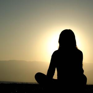 Silhouette of a woman sitting in front of the sun.