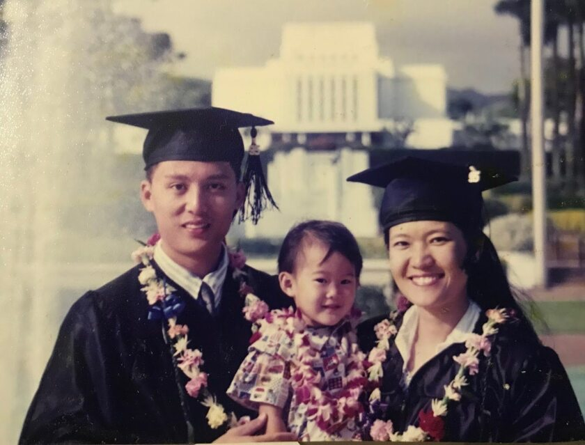 Photo of Joyce Tan and her husband wearing graduation caps and gowns holding their son all wearing leis with the Laie Hawaii Temple in the background.