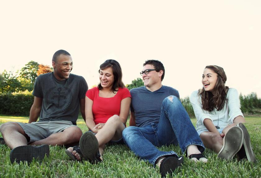 smiling-women-and-men-sitting-on-green-grass-1231230.jpg